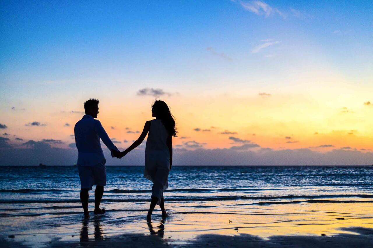 man-and-woman-holding-hands-walking-on-seashore-during-1024960