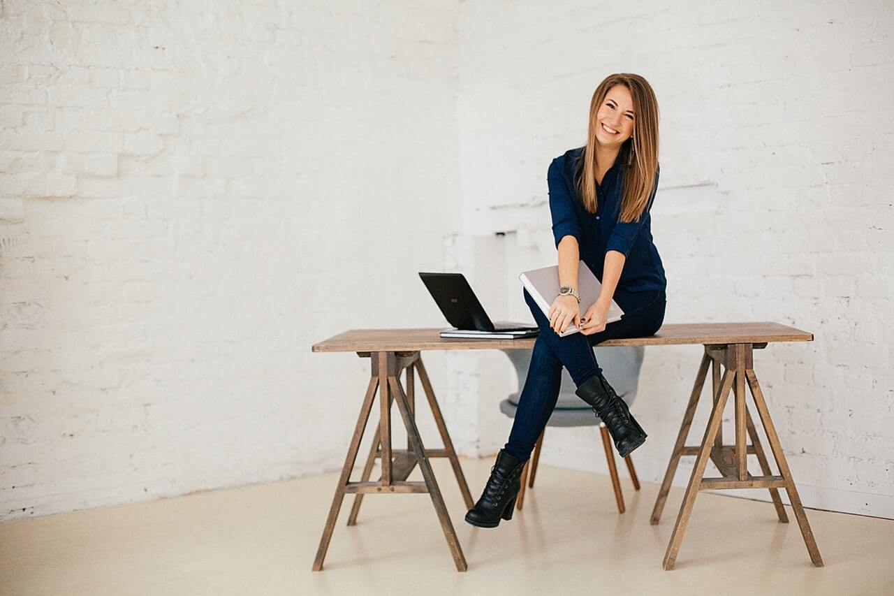 woman-holding-a-book-sitting-on-a-wooden-table-3681610
