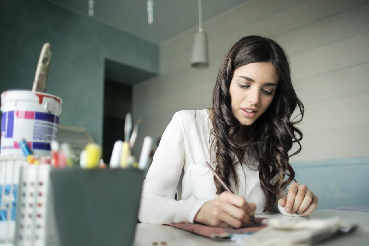 woman-sitting-while-holding-pen-920377